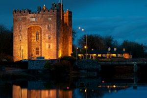 Bunratty Castle by night with Durty Nellys beside it